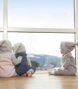 Tre heldresser med hette, foran vindu
